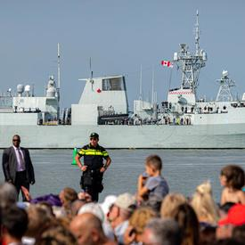 A photo of the crowd in attendance at the commemorative ceremony in Terneuzen, a military frigate in the background.