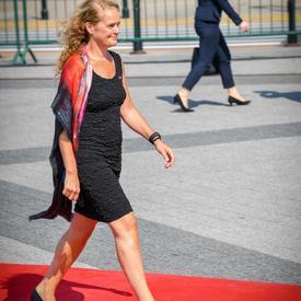 La gouverneure générale marche sur un tapis rouge en direction de son siège lors de la cérémonie commémorative.