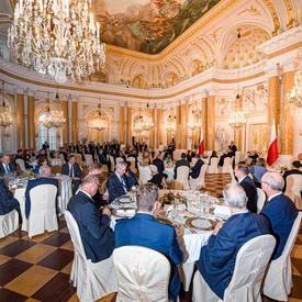 Une photo des chefs d'État assis à des tables à l'intérieur du château royal de Varsovie.