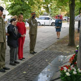 Deux officiers polonais et un ancien combattant polonais saluent un monument aux côtés de la gouverneure générale.