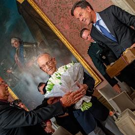 Le premier ministre des Pays-Bas remet des tulipes et une boîte de bulbes à l'ancien combattant canadien Don White.