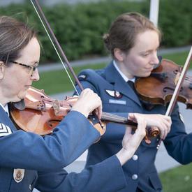 Des musiciens des Forces armées canadiennes jouent au cours d'une cérémonie extérieure de l'Ordre du Canada.