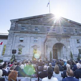 Photo d'une foule assise à l'extérieur de l'entrée principale de Rideau Hall lors d'une cérémonie extérieure de l'Ordre du Canada.