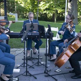 Une photo de musiciens des Forces armées canadiennes jouant lors d'une cérémonie mixte à l'extérieur de Rideau Hall.