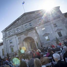 Une photo de l'entrée principale de Rideau Hall, avec des invités assis pour une cérémonie.