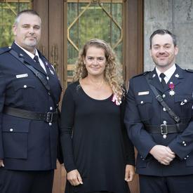La gouverneure générale se tient entre deux récipiendaires de la Médaille de la bravoure pour une photo.