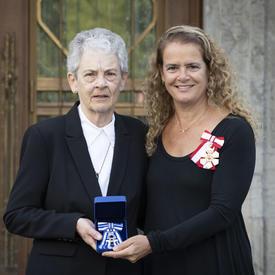 La gouverneure générale prend une photo avec un récipiendaire de la Croix du service méritoire.