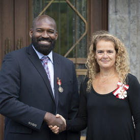 La gouverneure générale serre la main d'un récipiendaire lors de la cérémonie des distinctions honorifiques mixtes.