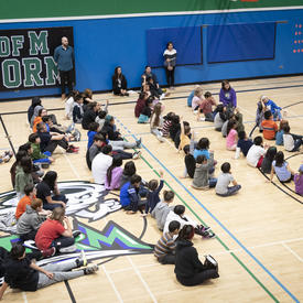 The Governor General speaking to students in a gymnasium.