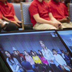 A picture of students seated in the Tent Room of Rideau Hall, with a virtual classroom from Vancouver on a screen.