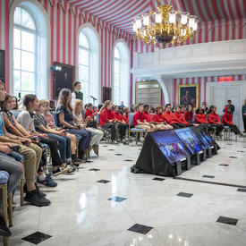 Over one hundred students and teachers sit and face the Governor General in the Tent Room of Rideau Hall as they engage in a question and answer session.