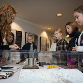 Students are shown elements from the Dare to Dream exhibit by an employee of the Office of the Secretary to the Governor General.