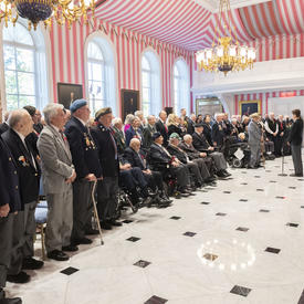 A large group of veterans stand in solidarity during the singing of the National Anthem at the launch of the 2019 National Poppy Campaign.