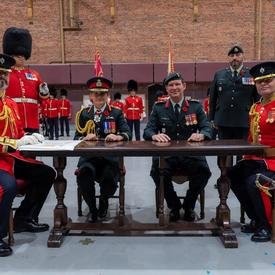 The Governor General takes part in the official signing of the Change of Command certificates.