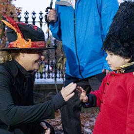 La gouverneure générale salue un jeune visiteur.