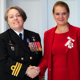La gouverneure générale serre la main du capitaine de frégate Burke.