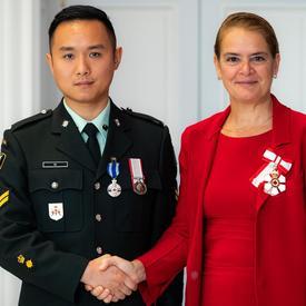La gouverneure générale serre la main du caporal-chef Yu.