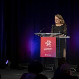 La gouverneure générale Julie Payette est à un podium, sous les projecteurs. La scène est très sombre derrière elle.