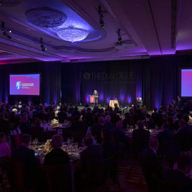 La gouverneure générale du Canada Julie Payette sur une estrade sur scène, vue du fond d'une grande salle sombre avec quelques lumières violettes et roses.