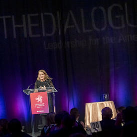 La gouverneure générale du Canada Julie Payette sur scène. La scène est sombre derrière elle. Quelques lumières violettes et roses sont projetées sur un grand rideau noir derrière elle.