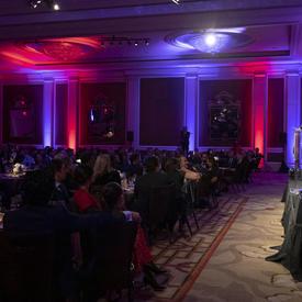 Vue de côté d'une salle où la gouverneure générale Julie Payette est vue, à l'extrême droite de la photo, sur scène, à un podium. La pièce est très sombre mais il y a des lumières violettes et roses.