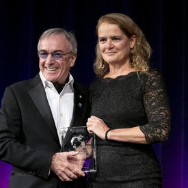 Daniel Lamarre, président et chef de la direction du Cirque du Soleil, et la gouverneure générale du Canada Julie Payette tiennent un prix fait de verre transparent dans leurs mains.