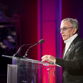Vue de droite de Daniel Lamarre, président du Cirque du Soleil, à un podium transparent, prononçant une allocution.
