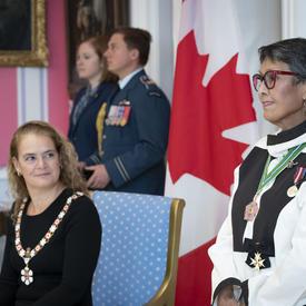 La gouverneure générale observe comment un récipiendaire est investi dans l'Ordre du Canada.
