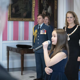 The National Anthem is sung by a young lady at the Order of Canada ceremony.