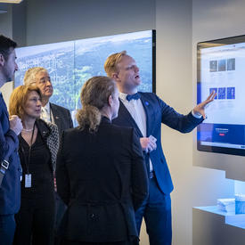 The Governor General and members of the delegation are looking at a screen.