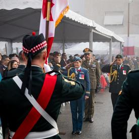 Governer General Julie Payette, wearing the Canadian Air Force uniform is saluting troops.
