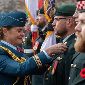 La gouverneure générale Julie Payette, portant l'uniforme de l'armée aérienne du Canada, ajuste un coquelicot sur l'uniforme d'un membre des Forces canadiennes.