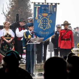 Governor General Julie Payette, wearing the Canadian Air Forces uniform is delivering a speech at a podium at Pontecorvo Monument.