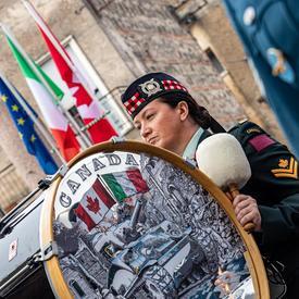 Un membre de l'orchestre de cornemuses et tambours des Forces armées canadiennes tient un tambour de cuivre.