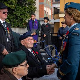 Governor General Julie Payette, wearing the Canadian Air Forces, is mingling outside with veterans.