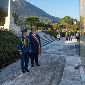 La gouverneure générale Julie Payette, en uniforme des Forces aériennes canadiennes, se tient devant un monument en compagnie du maire de la ville, à Cassino.
