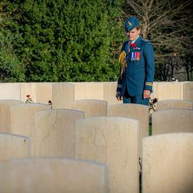 Governor General Julie Payette, wearing the Canadian Air Forces uniform is seen from a distance, visiting the Cassino War Cemetery.