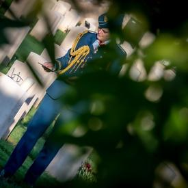 Governor General Julie Payette, wearing the Canadian Air Forces uniform is seen from a distance, in the shadow of a tree, visiting the Cassino War Cemetery.
