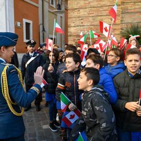 La gouverneure générale salue un groupe d'enfants ayant des drapeaux canadiens et italiens à la main.