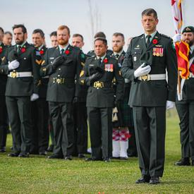 Canadian Armed Forces members stand with their hands over their hearts.