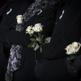 Une photo de dignitaires tenant des roses blanches en l'honneur des 14 femmes décédées.