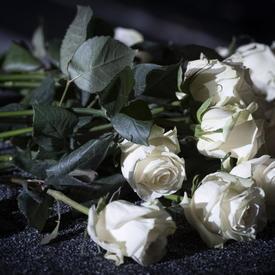 Des roses blanches posées sur une table lors de la cérémonie commémorative de la Polytechnique.