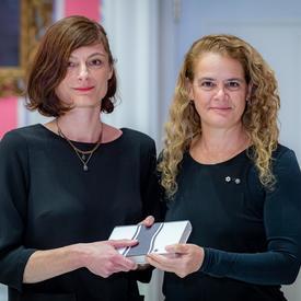 Céline Huyghebaert se tient aux côtés de la gouverneure générale.