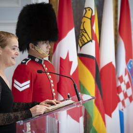 La gouverneure générale prononce une allocution à un podium, des drapeaux nationaux et un garde de cérémonie derrière.