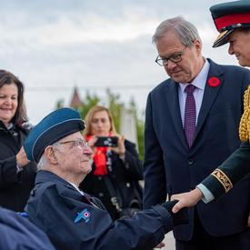 The Governor General shakes hands with veterans.