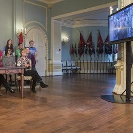 Le premier ministre, la gouverneure générale et l'épouse de David Saint-Jacques, Véronique Morin, sont assis autour d'une table et regard un écran de télévision. Un groupe d'étudiants est assis derrière eux.