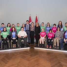 Le premier ministre, la gouverneure générale et l'épouse de David Saint-Jacques, Véronique Morin, prennent une photo de groupe avec le groupe d`étudiant.