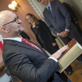 A gentleman, standing, has is right hand over the bible to deliver an oath.