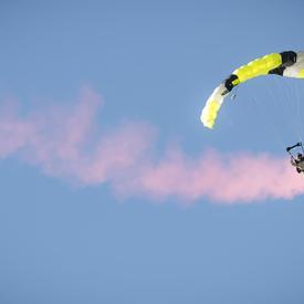 Un membre des Forces armées canadiennes descend du ciel en parachute.