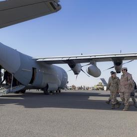 La gouverneure générale marche aux côtés des membres de la FCA. Un avion est à l'arrière-plan.